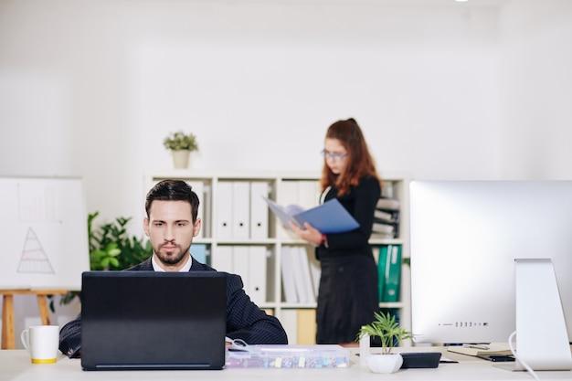 Молодой серьезный бизнесмен работает на ноутбуке, когда его коллега-женщина читает документ в папке в фоновом режиме