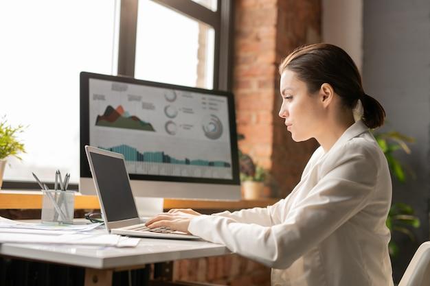 Молодая серьезная бизнес-леди в формальной одежде, сосредоточенная на финансовом анализе, сидя перед ноутбуком в офисе