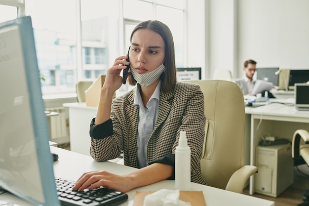 Молодой серьезный бизнесмен нажимает клавишу клавиатуры, глядя на экран компьютера и разговаривая с кем-то на смартфоне на работе