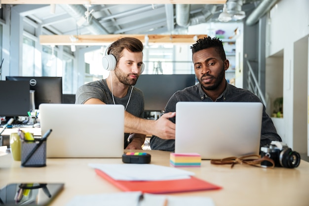 Giovani colleghi seri seduti in ufficio coworking