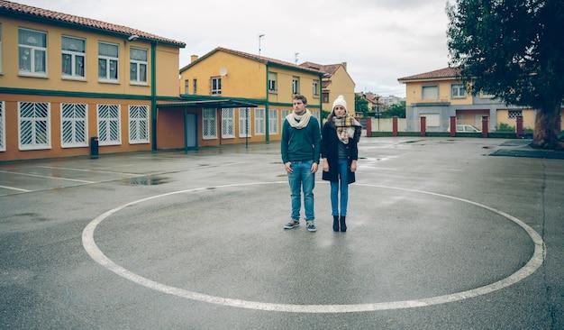 Молодая серьезная пара, стоящая внутри круга, нарисованного на полу на открытом воздухе. концепция отношений любви и пары.