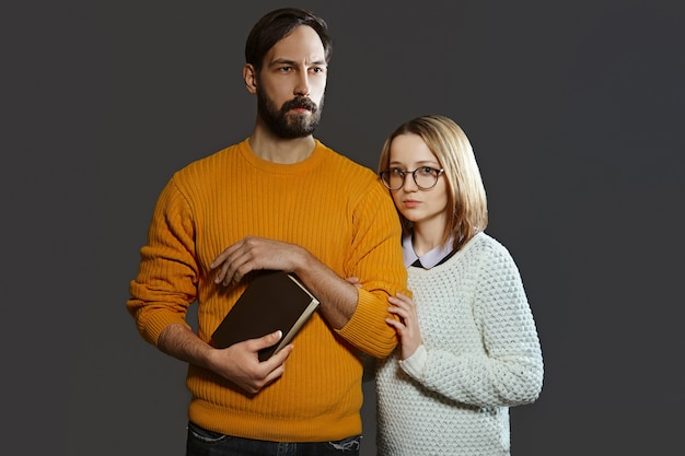 Young serious couple with man holding a book and woman with glasses