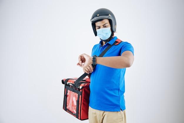 クーラーバッグを運び、スマートウォッチで時間をチェックするヘルメットと医療マスクの若い深刻な宅配便