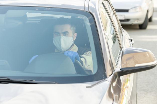 彼の車に座って検疫中に商品を配達しながらクライアントに運転している保護マスクと手袋の若い深刻な宅配便