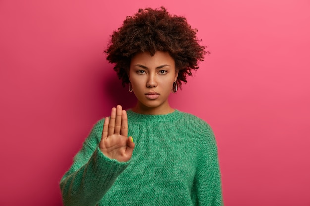 Young serious curly haired afro american woman does stop sign with palm, wears green sweater, demonstrates prohibition and restriction, refuses something, models against pink wall, says no