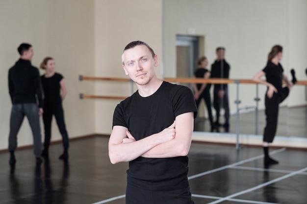 Молодой серьезный инструктор по танцам, скрестив руки за грудь во время позирования