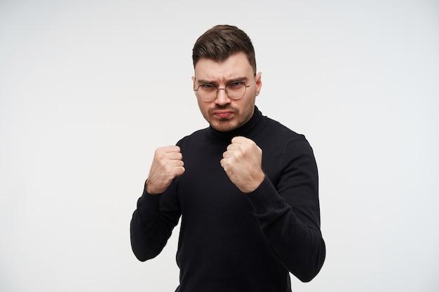 Giovane uomo dai capelli scuri serio con gli occhiali aggrottando le sopracciglia e alzando i pugni