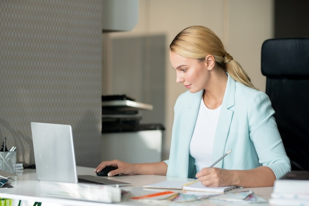 Молодой серьезный дизайнер делает заметки в блокноте, просматривая онлайн-сайты по месту работы