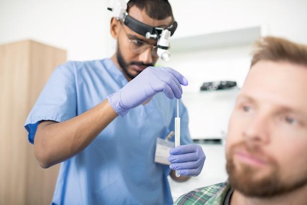Молодой серьезный врач в перчатках кладет медицинскую палочку в колбу перед обследованием и лечением пациента в больнице