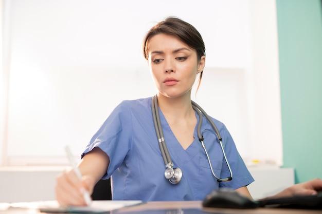 Молодой серьезный врач или стажер в синей форме делает рабочие заметки, сидя на рабочем месте перед компьютером