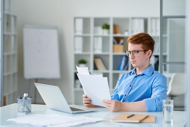 若い深刻な経済学者またはトレーダーが机に座っている間オフィスで財務書類を読んで
