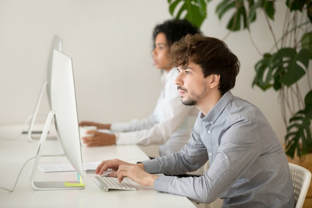Молодой серьезный работник сосредоточился на работе компьютера в многорасовом офисе