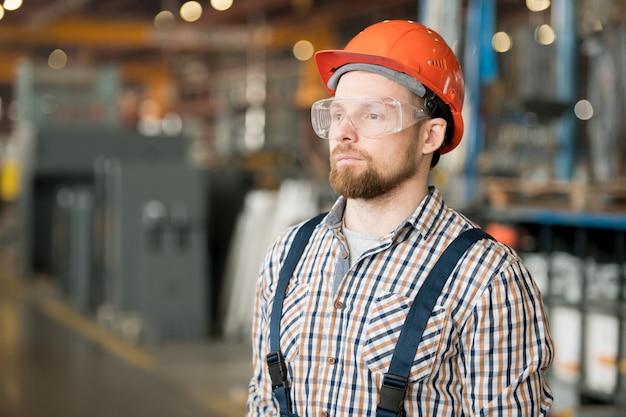 大規模な近代的な工場内のヘルメット、眼鏡、作業服の若い深刻なエンジニア