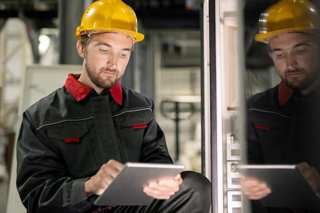 Молодой серьезный инженер в спецодежде и шлеме, просматривающий технические данные на цифровом планшете на одной из промышленных машин