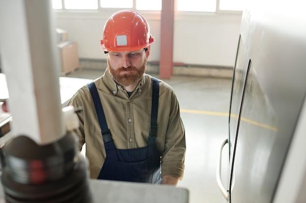 Молодой серьезный инженер с бородой стоит перед панелью управления в мастерской и выбирает, какую кнопку нажать