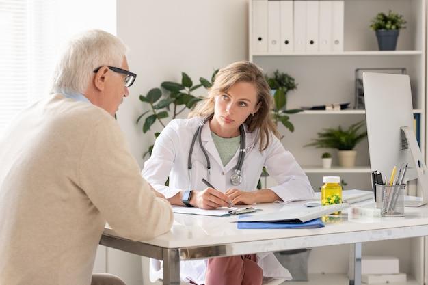 Молодая серьезная женщина-врач в белом халате смотрит на пожилого пациента, описывает симптомы и выписывает ему рецепты