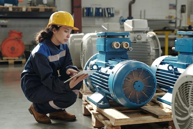 새로운 산업 장비로 쪼그리고 앉고 디지털 태블릿을 사용하는 보호용 헬멧과 작업복을 입은 젊은 여성 엔지니어