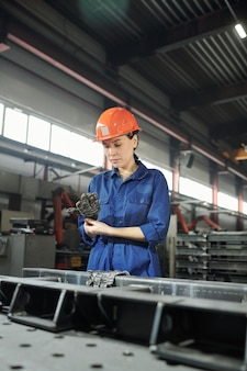 Young serious female engineer in workwear putting on gloves before work with huge iron details of industrial machine