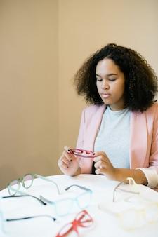 Молодая серьезная женщина в элегантном повседневном стиле смотрит на пару очков в руках с различными очками на столе