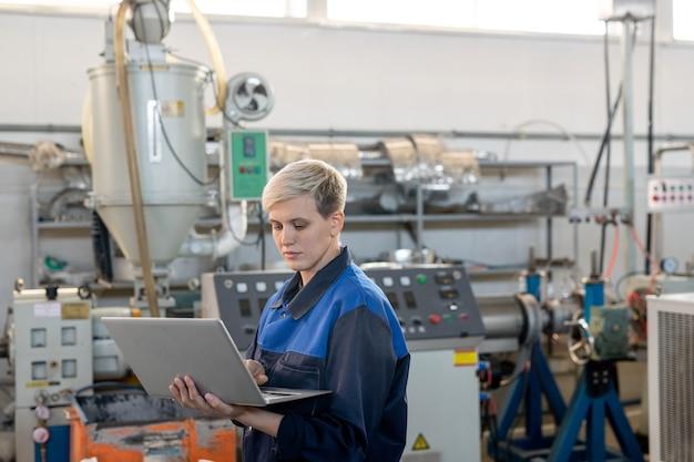 산업 기계에 대한 온라인 기술 데이터를 살펴보는 동안 노트북 디스플레이를 보고 있는 작업복을 입은 젊은 진지한 여성 노동자