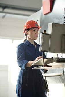 Young serious female worker in uniform and helmet looking at screen of control panel while operating with technical data