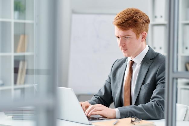 オフィスで働いている間ノートパソコンのディスプレイ上のオンラインデータを見て若い深刻な金融専門家