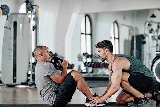 Молодой серьезный фитнес-тренер помогает зрелому клиенту делать приседания и скручивания на коврике в тренажерном зале