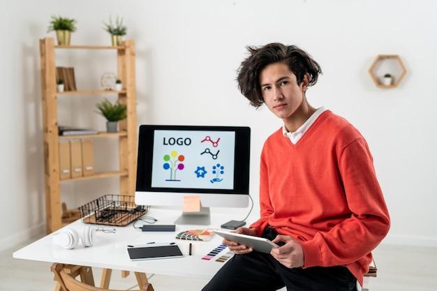 Молодой серьезный дизайнер-фрилансер использует тачпад, сидя на столе с рабочими принадлежностями на фоне