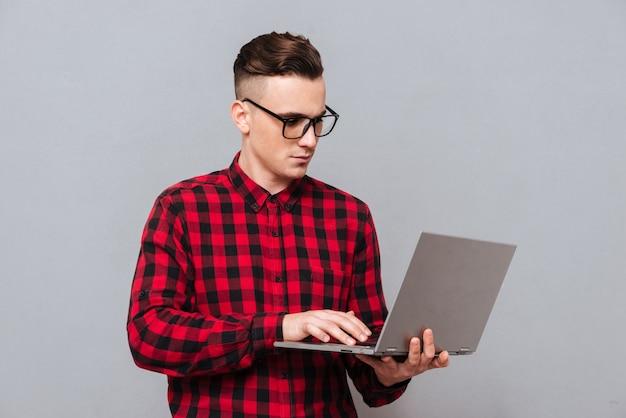 Молодой серьезный битник в очках и красной рубашке держит ноутбук в руках и что-то пишет. изолированный серый фон