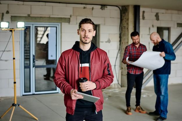 그의 동료가 청사진에 스케치를 논의하는 동안 음료와 태블릿 서 카메라 앞에 젊은 심각한 집 디자이너