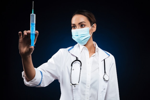 Young serious lady in medical mask holding and looking at syringe