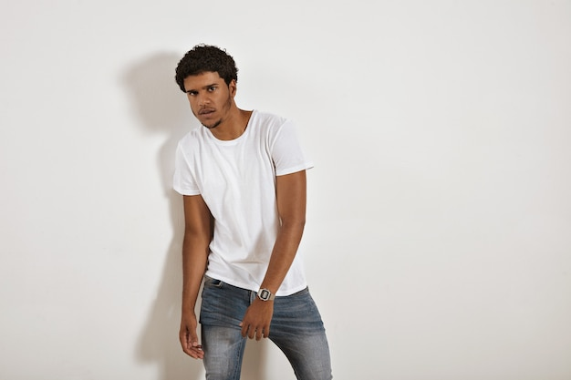 Young serious looking black model in jeans and blank white t-shirt on white wall