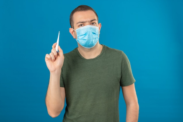 Young serious looking man wearing face medical mask holding a digital thermometer in raising hand isolated on blue
