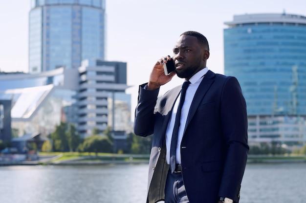 高層ビルや川沿いの街並みに立ち向かいながら、携帯電話でアフリカ民族コンサルティングクライアントの若い真面目な男性エージェント