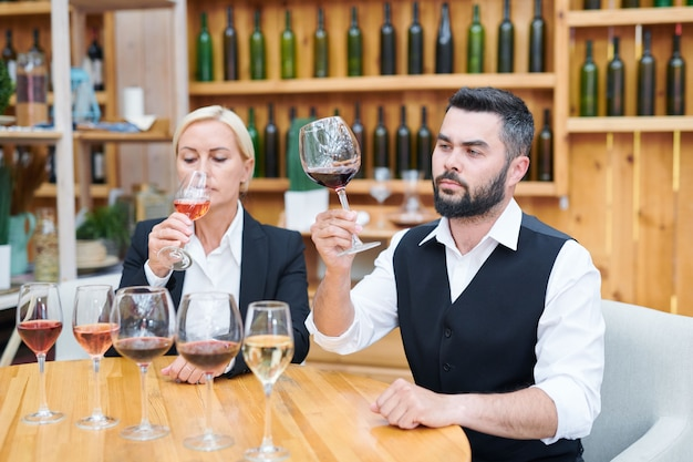 Young serious male cavist and his colleague checking smell and flavor of several new sorts of wine in cellar