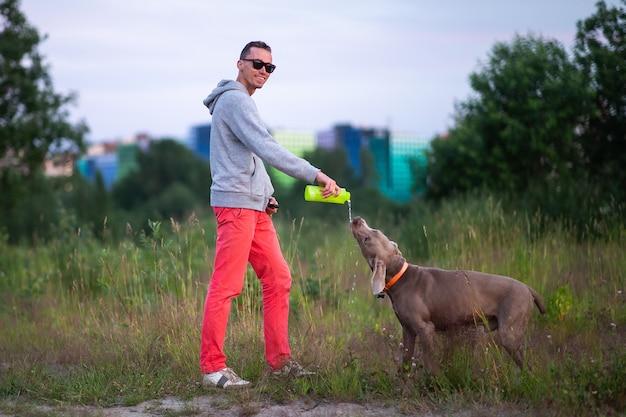 ワイマラナー犬と一緒に立っている灰色のパーカーの若い深刻な男性