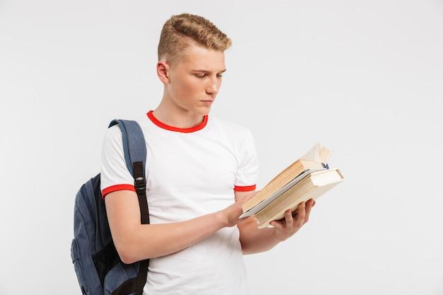 Молодой серьезный ученик носить рюкзак, изучение и чтение книг с концентрацией на белом