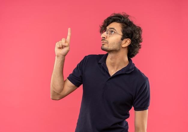 光学メガネと黒のシャツを着た若い真面目な男は、ピンクの壁に孤立して見えると上向き