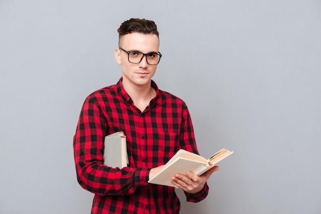 Молодой серьезный человек в очках и рубашке, держа книгу в руках