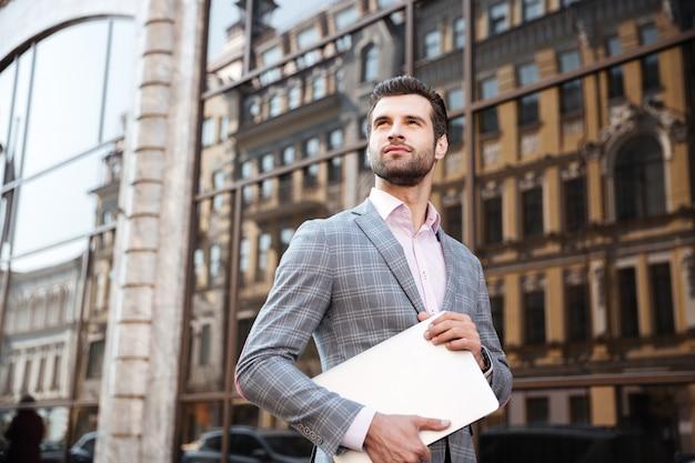 Молодой серьезный человек в куртке, держа портативный компьютер, стоя