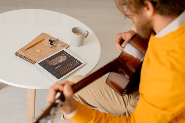 터치 패드를 사용하여 악기 튜닝 규칙을 검색하는 동안 기타를 굽히는 노란색 점퍼에 심각한 젊은이
