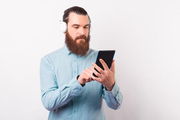若い真面目な男がタブレットを使用し、いくつかのイヤホンを着用しています。
