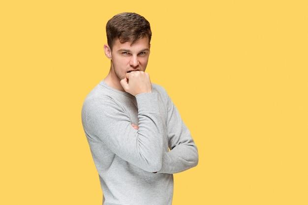 黄色のスタジオの背景を慎重に見ている若い真面目な男