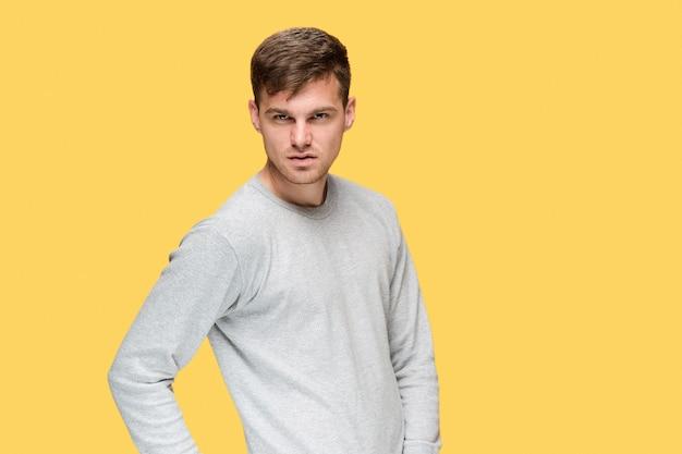 Il giovane uomo serio che guarda con cautela in studio giallo