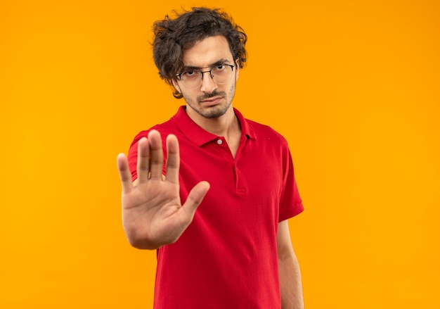 Young serious man in red shirt with optical glasses gestures stop hand sign isolated on orange wall