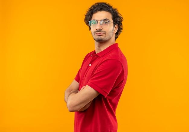 Giovane uomo serio in camicia rossa con vetri ottici si leva in piedi lateralmente e sembra isolato sulla parete arancione