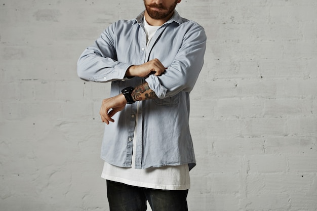 Молодой серьезный мужчина в белой футболке и голубой джинсовой рубашке, закатывая правый рукав, показывая татуированную руку, изолированную на белом.