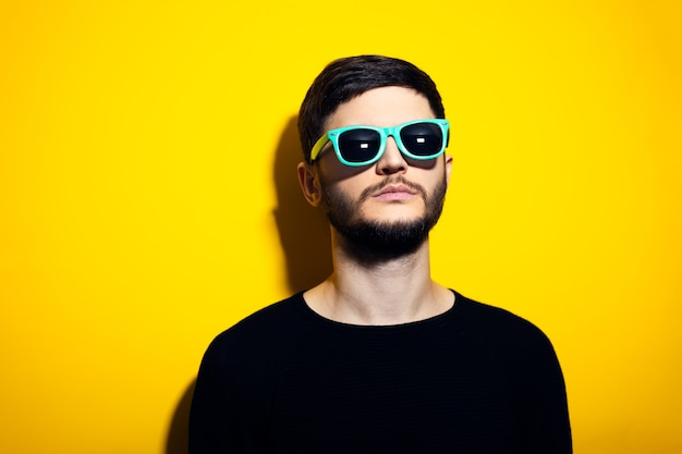 Young serious man wearing cyan sunglasses and black sweater on yellow wall.