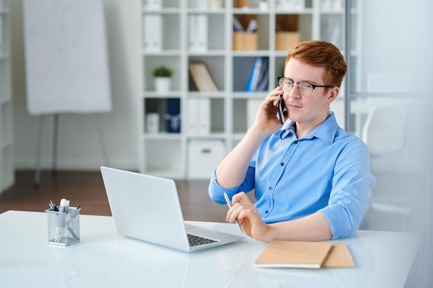 ノートパソコンの前の職場で座っている間スマートフォンで話している青いシャツを着て若い深刻なマネージャー