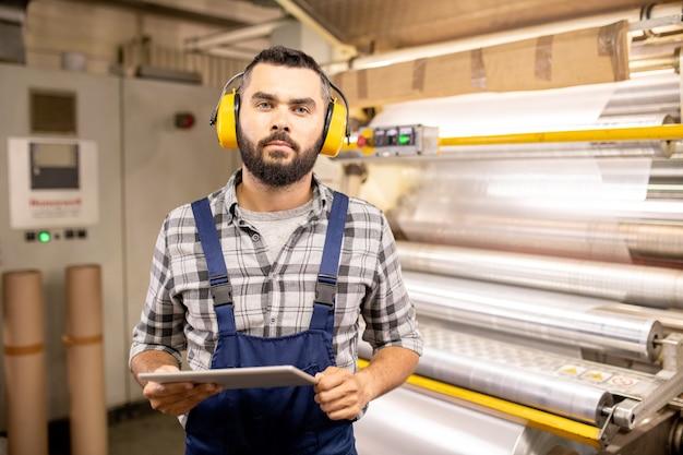 職場で品質管理作業をしながら、タッチパッドを使用してヘッドフォンで若い深刻な専門家